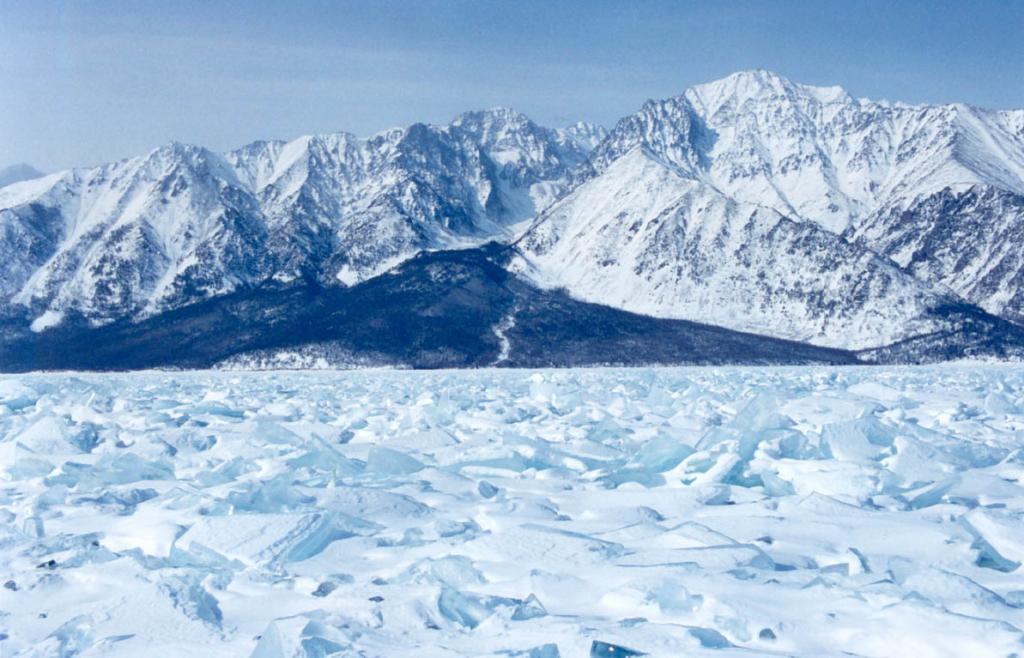 Сугробы из плотного и отшлифованного снега (заструги) на льду Байкала образованы сильным северо-западным ветром. На снимке: Байкальский хребет у мыса Большая Коса.