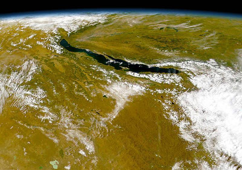 Если взглянуть на Байкал с очень большой высоты, перед взором предстанет огромная, продолговатая, зажатая между гор впадина. Гигантским, слегка вогнутым на восток полумесяцем, протянулась она далеко на север и северо-восток, в сторону Северо-Байкальского нагорья (белое справа).