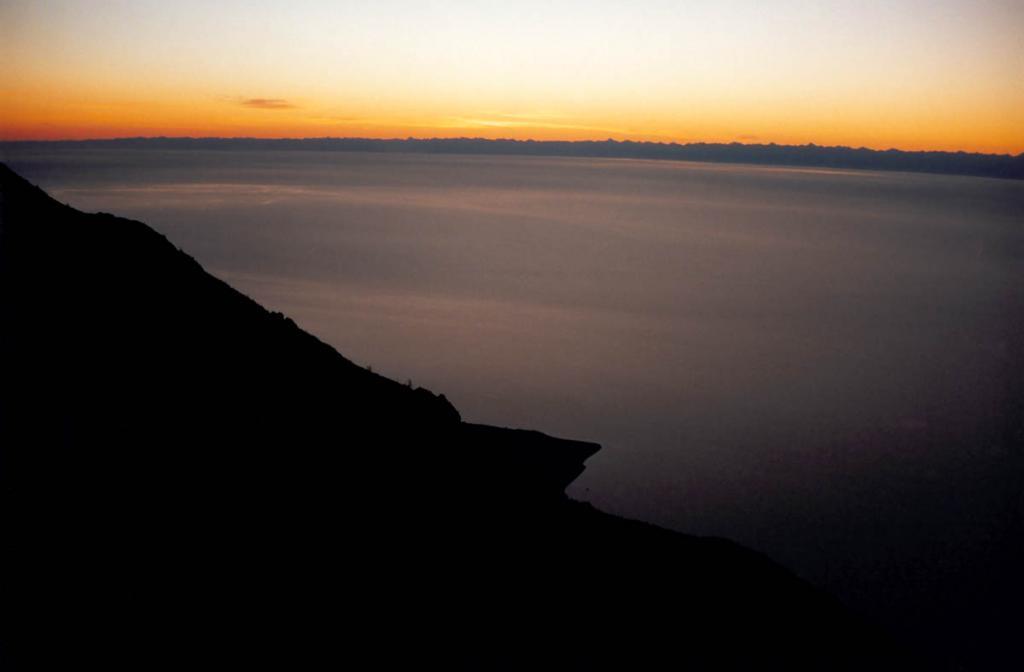 Над великим простором! Снимок сделан перед рассветом с вершины Байкальского хребта (район мыса Тытэри - виден внизу). На горизонте - Баргузинский хребет. (В нижнечетвертичное время эта (Северная) впадина Байкала была бессточной и полностью изолирована от Центральной. Водный бассейн впадины соединялся лишь с разрастающейся Маломорской впадиной).