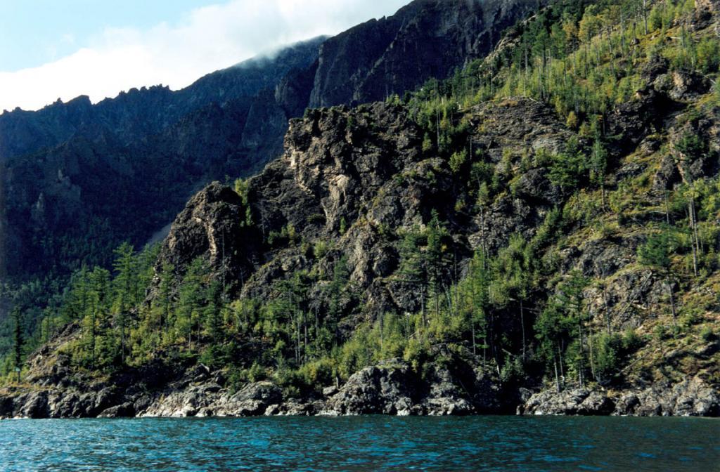 Крутые клоны с высокими скалистыми обрывами и отдельными каменными башнями южнее устья речки Ледяная круто обрываются к воде. Здесь осевая линия Байкальского хребта подходит к воде на 6-7 километров.