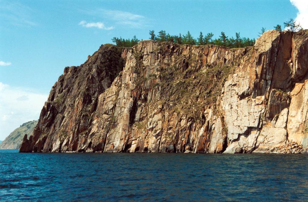 Западное побережье Байкала поражает своей неповторимой композицией разнообразных тектонических форм, их ансамбли единого происхождения, вплоть до небольших сейсмогенных дислокаций, доступны полному обзору со стороны озера. На снимке: скальные обрывы у мыса Кулгана - грозное предупреждение байкальским судам, проходящих здесь в сильные шторма.