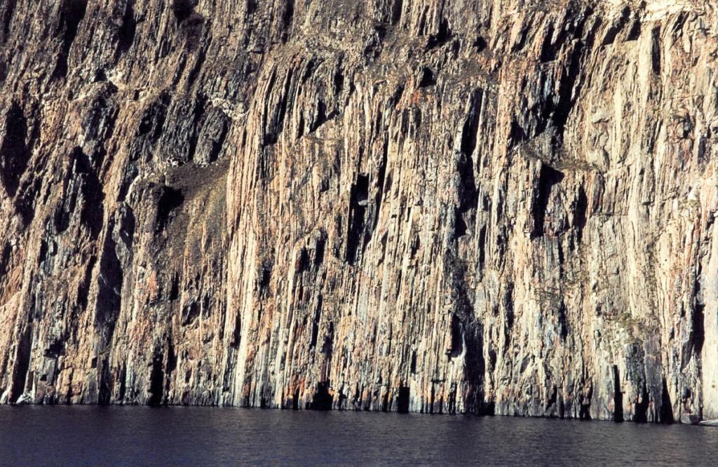 Переслаивающиеся основные сланцы отвесно обрываются к воде на северной оконечности острова у мыса Шунтэ Левый.