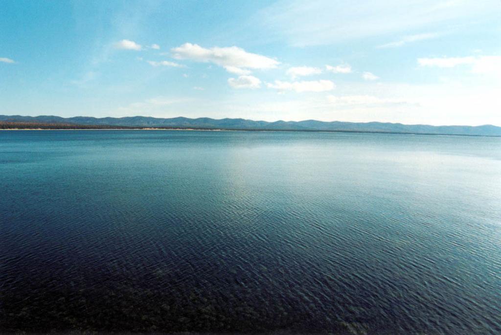 Особенной чертой центральной части восточного побережья Байкала (от села Максимиха до села Гремячинск) является обилие участков с эоловыми образованиями - песчаными дюнами (на снимке - желтая полоска у края воды). Горы у побережья - хребет Черная Грива. Снимок сделан с мыса Безымянный.