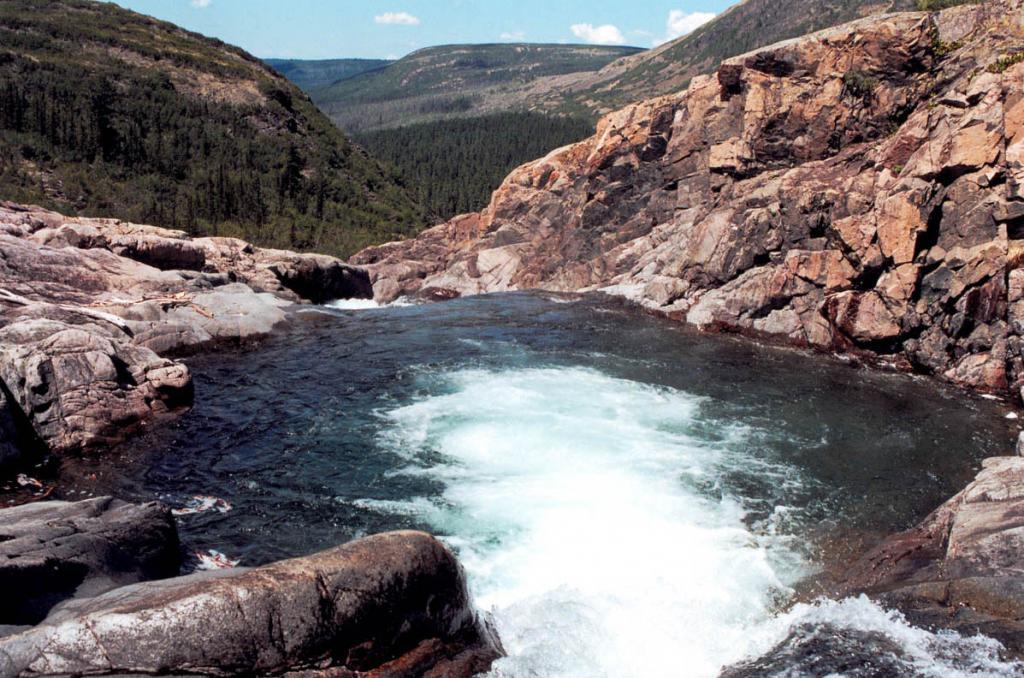 """Рельеф гор, окружающих Северный Байкал, сформирован оледенениями. На выровненных вершинных поверхностях хребтов формировались мощные (до 500 м.) ледники покровного и сетчатого типа, которые при спуске с вершин хребтов переходили в горно-долинные. На снимке: первая чаша каскада """"Чудо Тонгоды""""."""