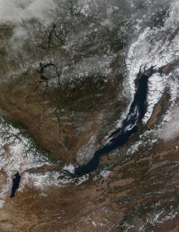 На снимке, сделанном спутником НАСА, видно, как хребты, обрамляющие байкальскую впадину, то вплотную подступают к воде, то оставляют небольшие участки прибрежных низменностей. Поднимаются горы на 1000-2000 метров над уровнем воды в озере. Впадину окружают крутые, местами обрывистые, залесенные склоны хребтов, изобилующие осыпями и каменными потоками - курумами. Узкие, ущельевидные, глубокие долины рек и ручьев, густо расчленяющие горные склоны, имеют круто падающее дно, нередко заграможденное каменистыми о