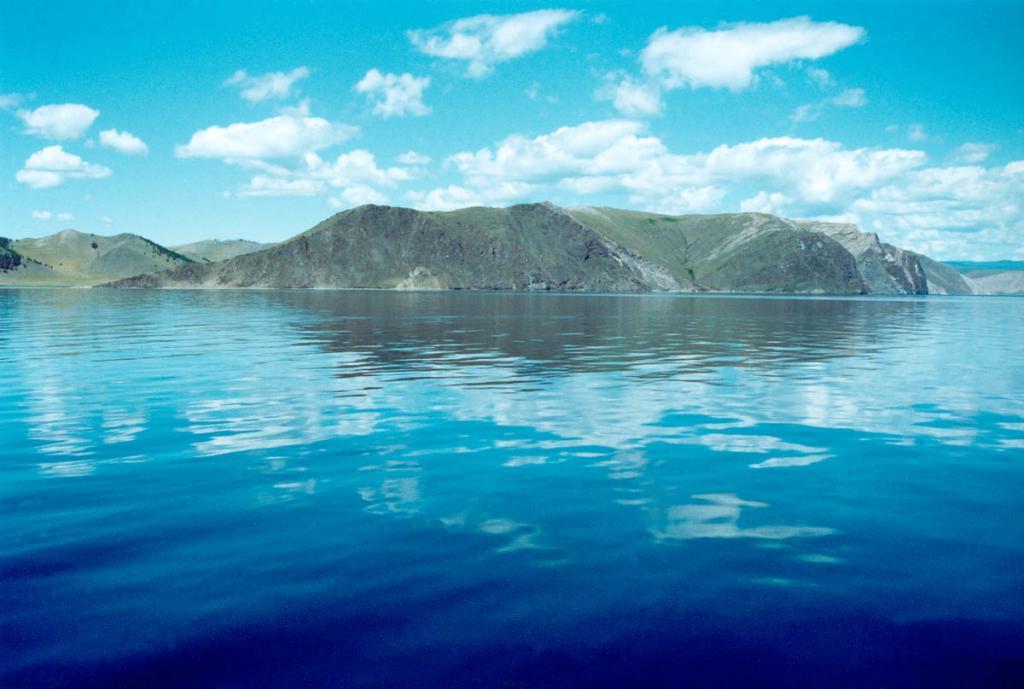 Средняя часть западного побережья Байкала вплоть до пролива Ольхонские ворота в основном образована крутыми, часто скалистыми берегами, расчлененными долинами рек и небольшими распадками ручьев. Здесь широко распространен холмисто-увалистый и гриво-ложбинный рельеф с общим субгоризонтальным уровнем - реликтом мел-палеогенового пенеплена, который выработан на докембрийских мраморах и кристаллических сланцах с повсеместным выходом на поверхность небольших останцевых скал и мелких гряд. На снимке: побережье с