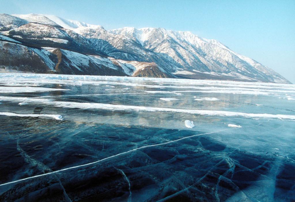 Снежный покров на льду Байкала распределяется неравномерно в основном из-за частых сильных ветров. Лед вдоль западного побережья часто малоснежный или бесснежный. На снимке: Байкал у мыса Хыр-Хушуун (Рытый). Начало марта.