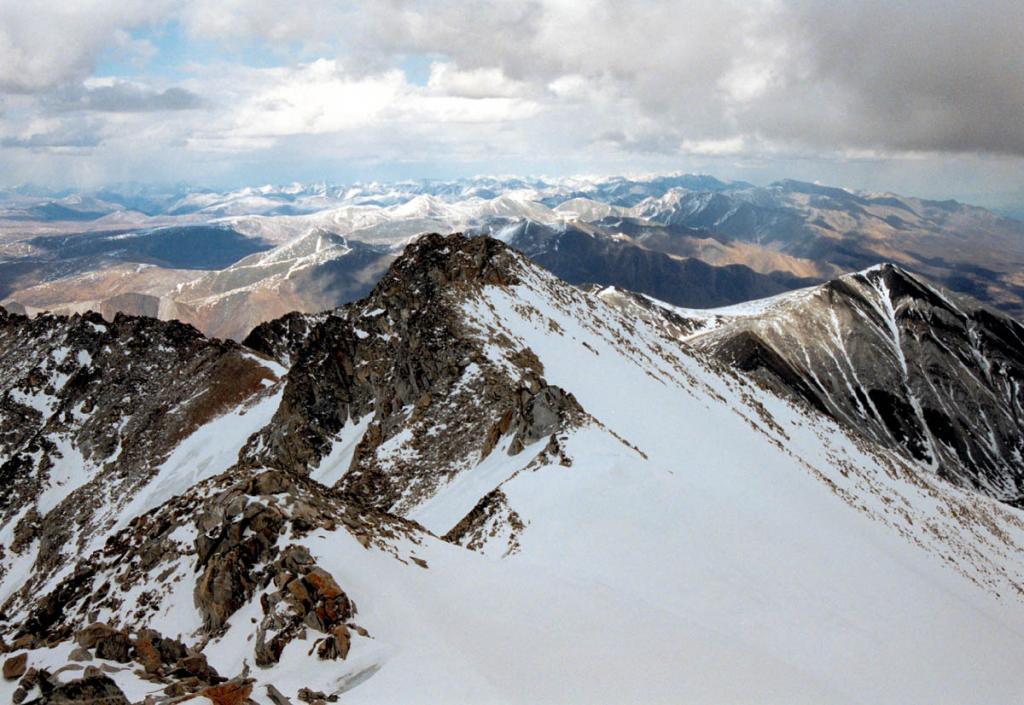 Все вершины Мунку-Сардык поднимаются выше снеговой линии. Склоны круто обрываются на север (на снимке влево) и более полого спускаются к югу, к озеру Хубсугул. На снимке: скалистые вершины юго-восточного гребня Мунку-Сардык, справа - вершина южного ледника (наклон поля ледника - от 10 до 45 градусов).