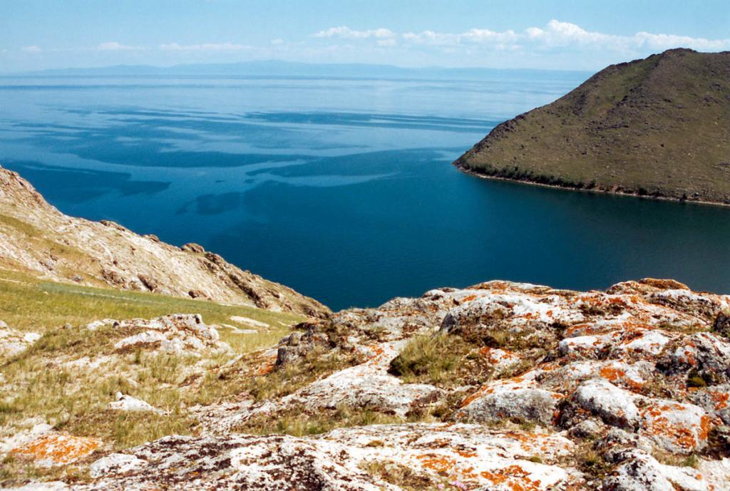 Над входом в красивейшую на западном побережье Байкала бухту Ая возвышаются голые горы, сложенные лейкократовыми гранитами, пегматитами с амазонитами, карбонатными породами. Камни на переднем плане покрыты накипными лишайниками. Ширина бухты в устьевой части 600 метров. Ширина Байкала в этом месте - 36 километров.