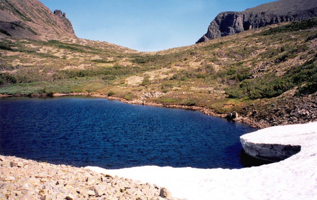Небольшое безымянное озеро на перевале Заворотненском (1600 м над ур.м.) зимой занесено толстым слоем снега. Последний снежник на берегу озера исчезает в середине июля.