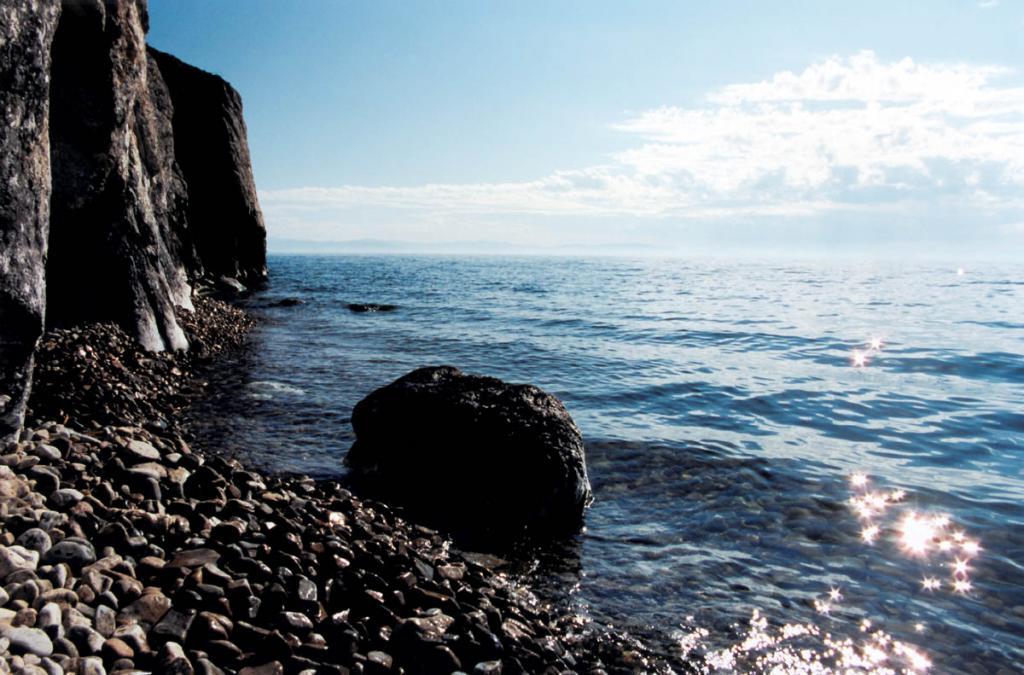 Юго-восточные склоны у Нижнего Изголовья полуострова Святой Нос часто обрываются в Баргузинский залив отвесными скалами. На горизонте - вершины Баргузинского хребта.