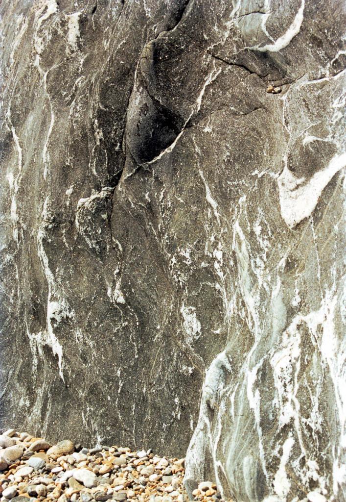 Породы первой Ольхонской серии представляли собой осадочно-вулканогенную толщу, в которой излияния толеитовых базальтов повышенной железистости чередовались с периодами хемогенного осаждения кремнистых осадков с проявлением гидротермальной вулканической деятельности. Последние данные (В.С. Федоровского) говорят о палеозойском возрасте исходных пород ольхонской серии. На снимке: основание скалы на мысе Ухан (восточный берег Ольхона).
