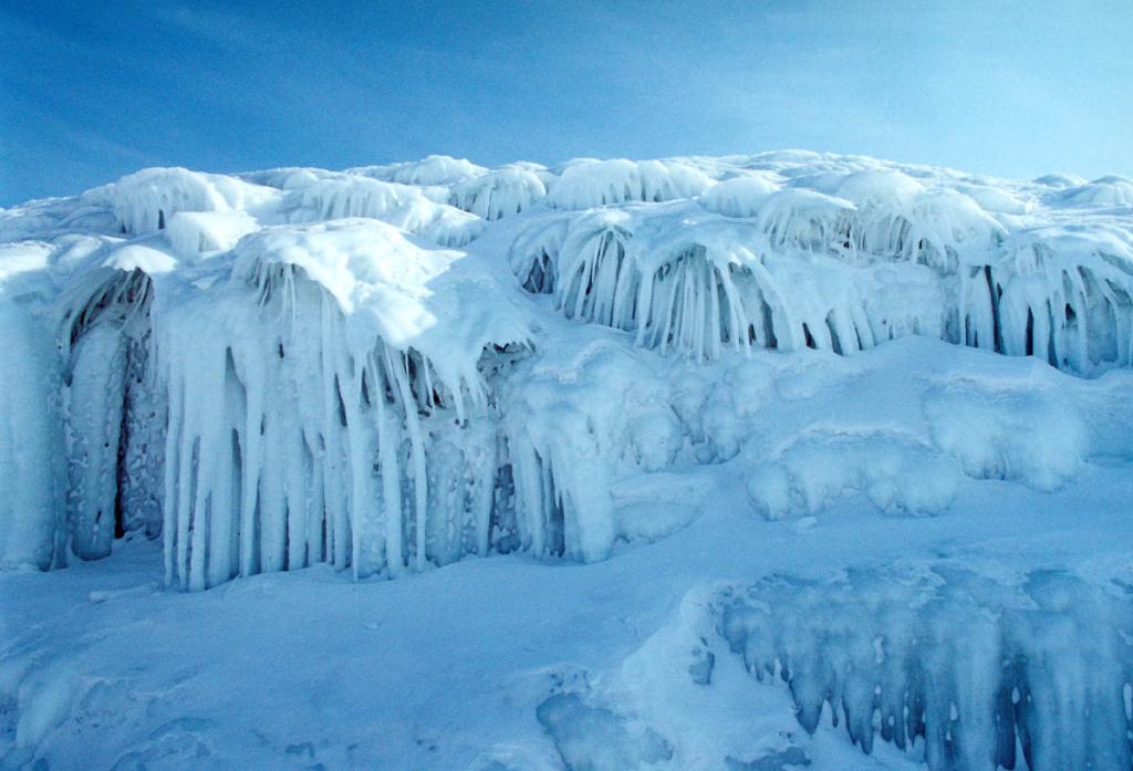 """Сон заповедного берега - такими открываются берега Ольхона в зимние месяцы. Брызги разбивающихся о скалы декабрьских волн долетают до 13-метровой высоты. Стекая при минусовой температуре (до -25С) они замерзают, образуя причудливые ледяные """"кусты"""". На снимке: берег у мыса Хунгай."""