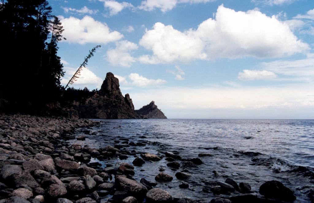 Скалы Малая и Большая Колокольня возвышаются у одного из самых известных мест западного побережья Байкала - бухты Песчаной. Уже в одном километре южнее бухты (на снимке) пески сменяются крупными галечниками.