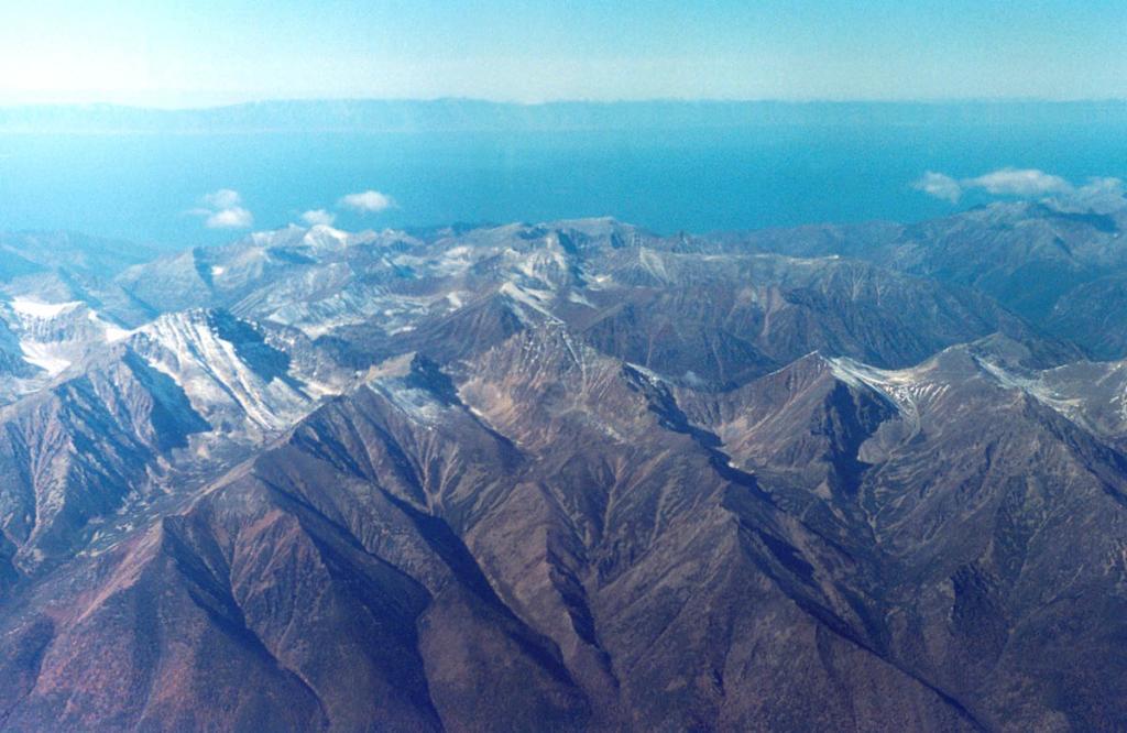 Комплексный анализ результатов глубоководных сейсмо-стратиграфических работ, проведенных на Байкале в последние годы, а также обобщение геолого-геоморфологических данных, позволили сделать вывод о значительной молодости современных контуров сибирского моря. На снимке: с борта самолета Байкал открывается огромной, продолговатой, зажатой между гор впадиной (длина тальвега озера 636 километров, расположено озеро между 51 градус 29 минут - 55 градусов 46 минут с. ш., 103 градуса 43 минуты - 109 градусов 56 мин