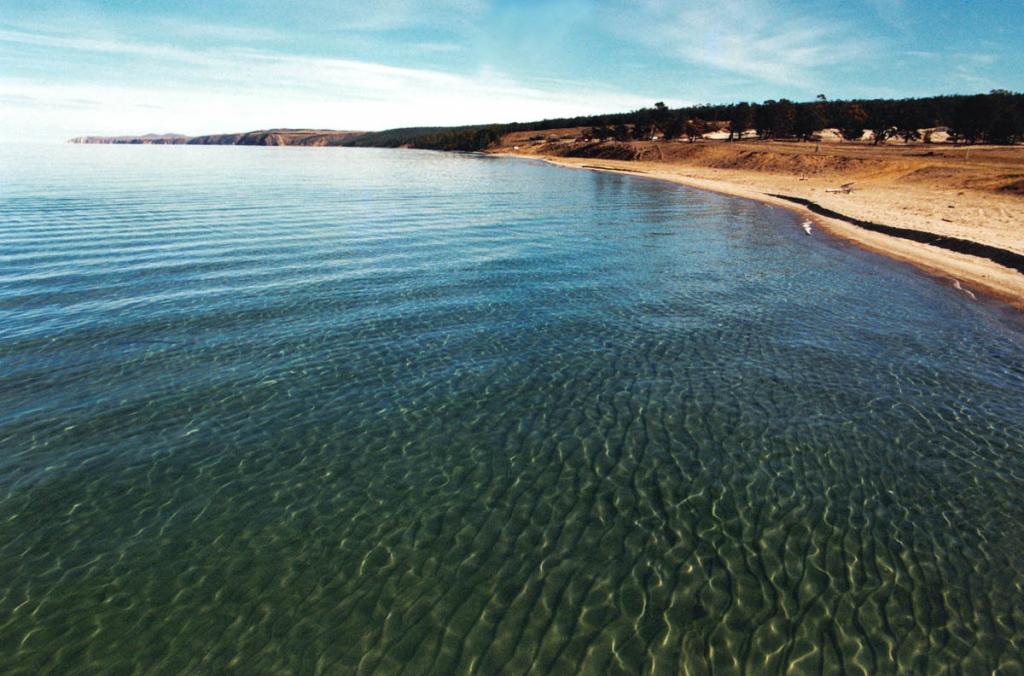 На острове Ольхон на небольшой площади (Сарайская бухта, Будунская губа, Нюрганская бухта) фрагментарно выделяются довольно пестрые кайнозойские отложения, сложенные зелеными глинами и светло-серыми песками. На снимке: лучший на Ольхоне 7-километровый песчаный пляж на берегу Нюрганской бухты.
