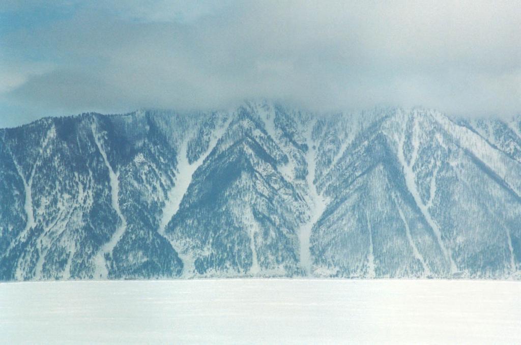 Крутой восточный склон полуострова Святой Нос, обрывающийся в Баргузинский залив, имеет множество узких распадков, лишенных древесной растительности. На снимке: восточный склон полуострова в районе мыса Толстый. Снимок сделан в марте.