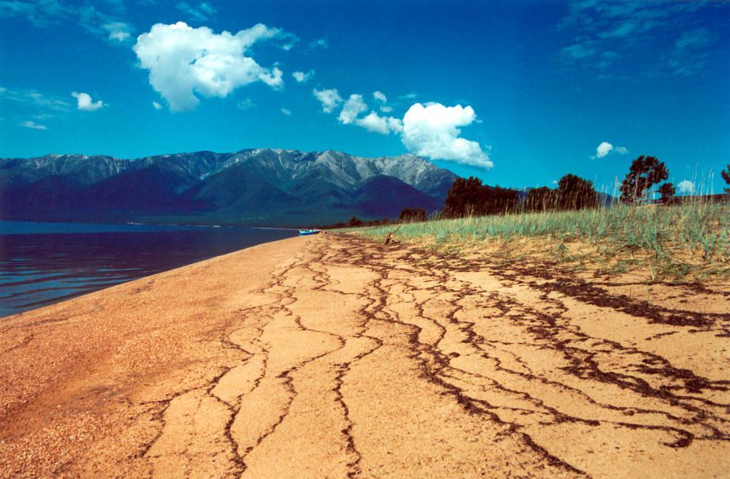 Полоски мелкой дресвы, принесенной волнами на святоносский перешеек, показывают характер накопления осадков, происходивших в основном по миграционной схеме: каждый вал был сформирован во время шторма в результате выброса крупными волнами на берег песка и гальки. Высота песчаного вала над уровнем залива - 1.7 - 2 метра. На снимке: уникальный, лучший на Байкале, святоносский песчаный пляж в районе урочища Ельзиха. Слева - Баргузинский залив.