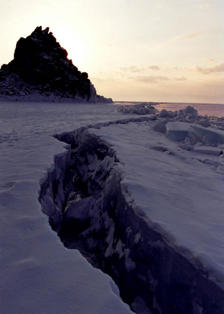 """Возникающие при понижении температуры сжимающие усилия во льду, встречая сопротивление изрезанных берегов, к которым """"припаян"""" панцирь по всему контуру озера, рвут лед на поля с размером сторон 10-30 километров, при этом между ними образуются термические швы, называемые на Байкале становыми щелями. Местоположение и направление щелей мало меняется, ширина их постоянно колеблется от 0.5 до 4 метров. На снимке: становая щель у скалы Шаманка (остров Ольхон)."""