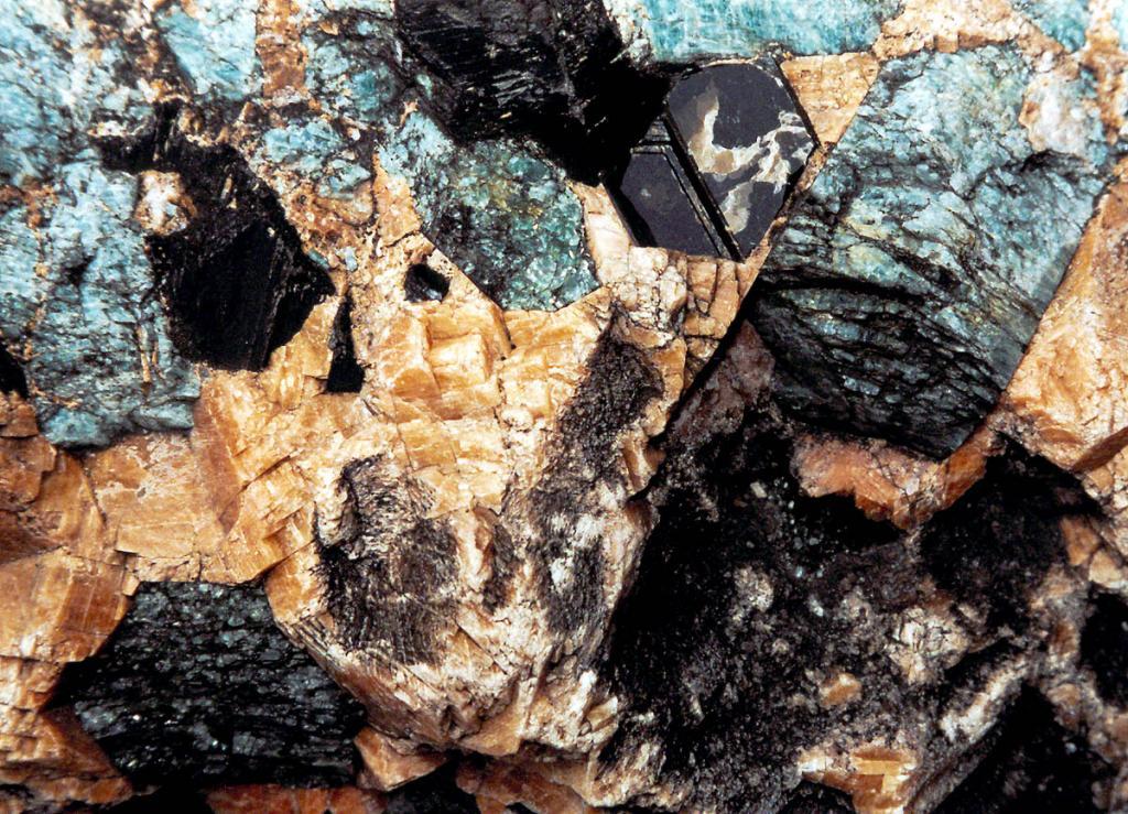 На снимке: Скарн, порода, образовавшаяся на контакте силикатного расплава и вмещающих мраморов. Основные минералы: апатит (светло-голубой), роговая обманка (черная с неровным ступенчатым изломом), кальцит (темно-желтый), ромбиками, слюда биотит (темная, почти черная) шестиугольные листочки.