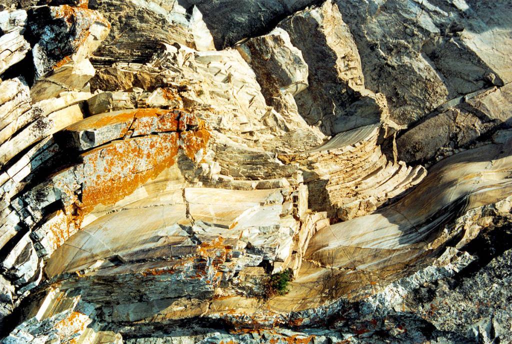 В составе вулканогенно-осадочных толщ Прибайкальской зоны входят стратифицированные образования (на снимке - Саган-Марянский разрез) базальт-диабазовой, базальт-риолитовой, спилит-кератофировой с базальтовыми коматиитами вулканогенных формаций. Эффузивы переслаиваются с туфами контрастного состава, граувакковыми песчаниками, зелеными парасланцами, железистыми кварцитами, реже карбонатными породами.