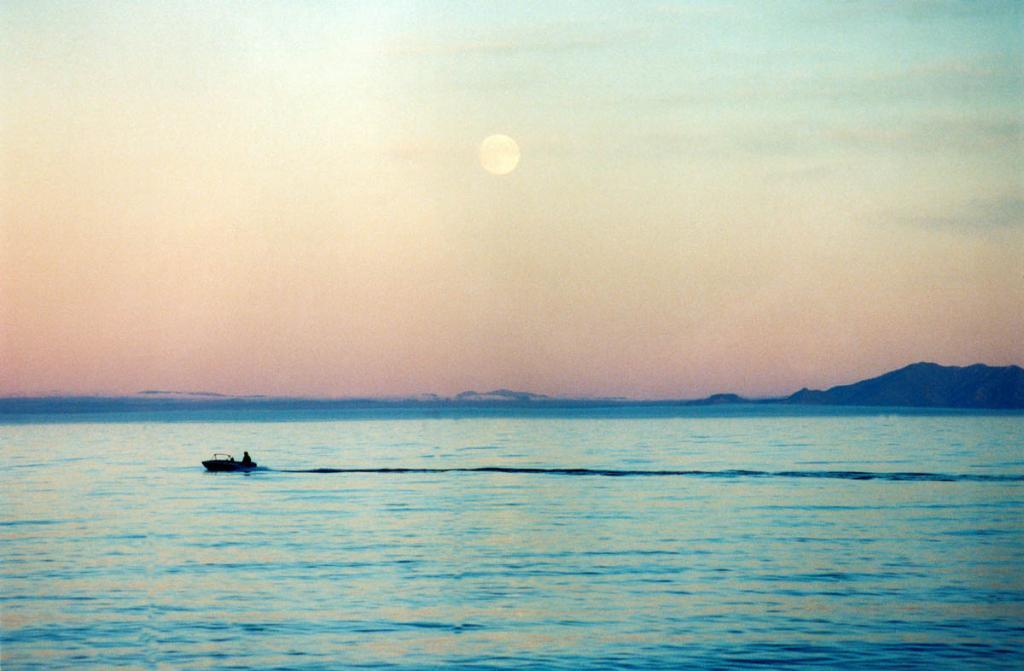 Байкал удивительно напоминает море: огромными размерами и глубинами, жестокими штормами, крутыми скалистыми берегами. Да и не принято было в стародавние времена называть Байкал озером, почтительно называли его только морем. Бирюзовая водная гладь Байкала нередко обманчива, не одного человека взяли к себе темные глубины. На снимке: на моторной лодке плывет мой добрый знакомый, опытный рыбак Владимир Бочаров. 8 марта 2002 года на этом месте его автомобиль УАЗ-462 провалился в ледовую щель и утонул. Из пяти п