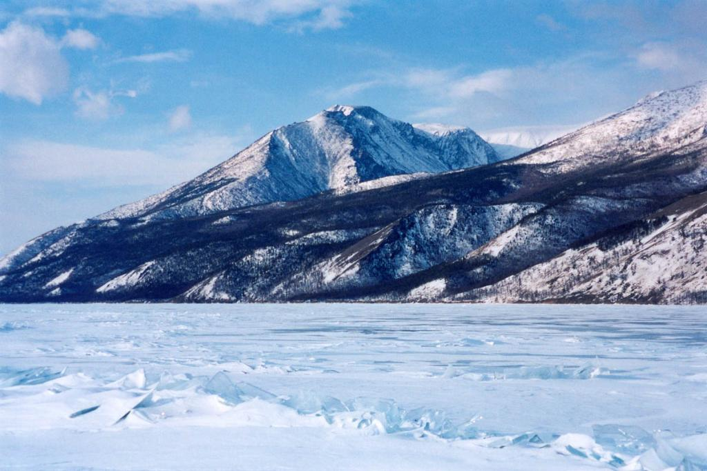 Зимой резкие формы горного северо-байкальского рельефа вместе с девственной тайгой на склонах придают хребтам суровую живописность. На снимке: Байкальский хребет у мыса Шартлай. БЛГЗ.