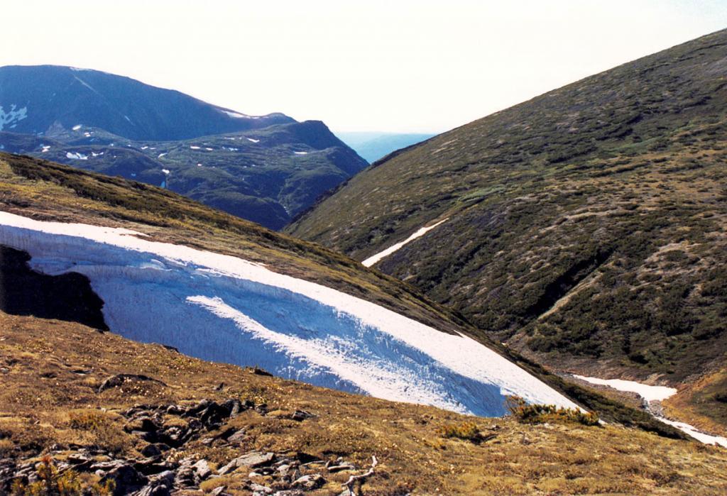 Медленно тающие снежники, разбросанные по горной тундре, - одна из характерных красок высокогорного мира Прибайкалья.