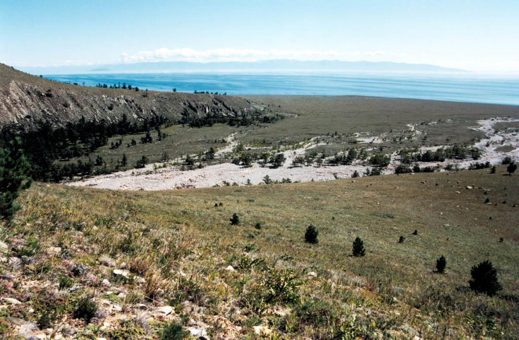 Галечниковое русло речки Риты на мысе Хыр-Хушуун (Рытый). Конус выноса этой речки самый большой на Байкале. Галечники, залегающие на древних образионных поверхностях по берегам речки, показывают, что уже в нижнем плейстоцене уровень Северного Байкала был на 120-150 метров выше современного.