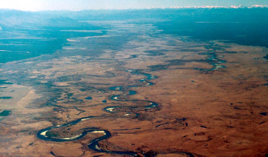 Извиваясь, распадаясь на множество протоков, медленно течет по широкой плоскодонной впадине река Баргузин. В далеком прошлом на месте долины существовало большое горное озеро, во многом напоминающее современный Байкал. Как и Байкал, оно со всех сторон было окружено хребтами: с северо-запада - Баргузинским, с юго-востока - Икатским. На снимке: северная часть Баргузинской долины, снимок сделан с борта самолета (через иллюминатор).