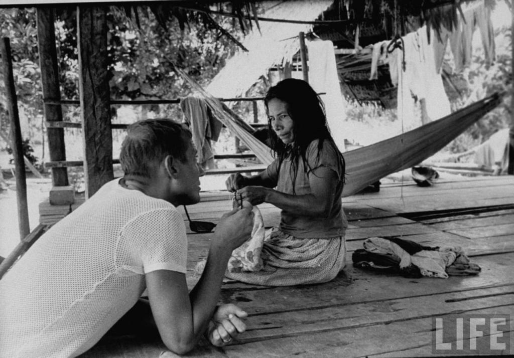 Евгений Евтушенко разговаривает с колумбийской женщиной во время похода на лодке по реке Амазонке.