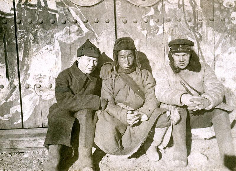 Красный командир и красноармеец с монгольским аратом (крестьянин) у ворот музея. Монголия, 1938-1939 гг.