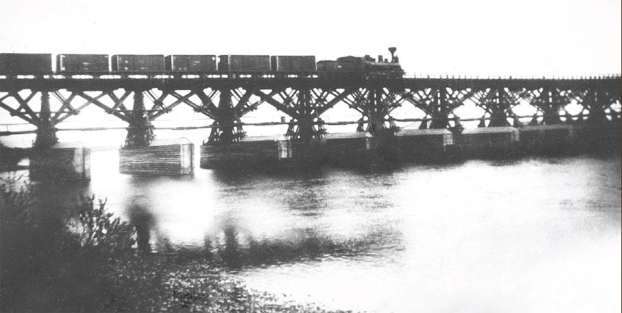 Железнодорожный поезд проходит по мосту, сооруженному на деревянных сваях. Фото. 1900-е.