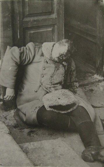 Изуродованное тело человека, прислоненное к дверному проему