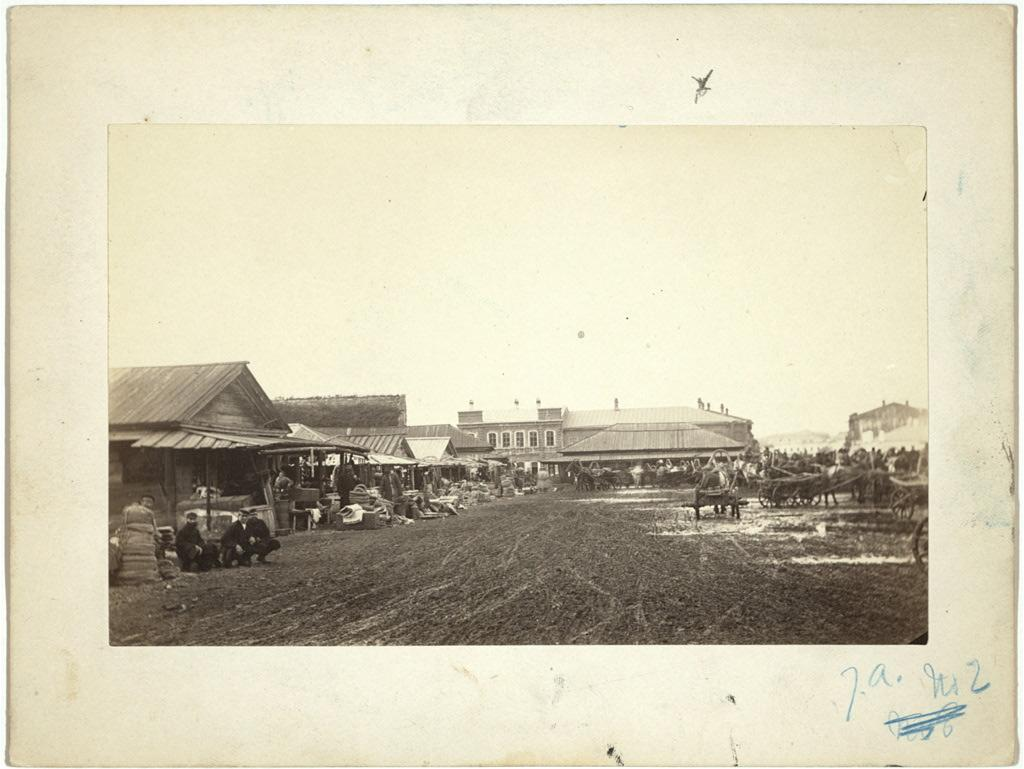 Шумный рынок в Иркутске, с типичными сибирскими однолошадными повозками.