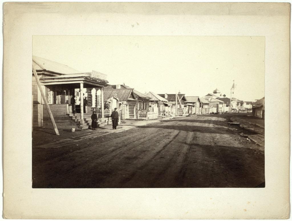 Улица с деревянными домами и немощенной мостовой. 1885