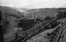 """Проходка участка """"решающий"""". Железная дорога выходит из штольни, вывозя вагонетки со слюдой к дробильной установке."""
