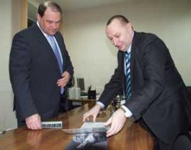 Председатель ИГТРК Леонид Гунин демонстрирует Игорю Есиповскому альбомы с фотографиями сотрудников телекомпании